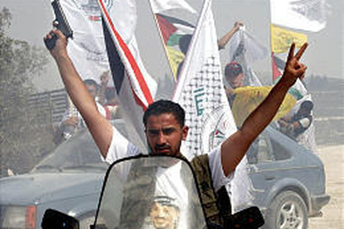 A Palestinian man holds a pistol as he and others celebrate while driving through an evacuated West Bank Jewish settlement.