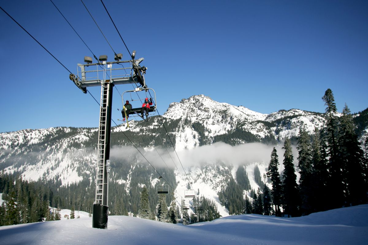 Two people ride a ski lift. In the foreground, a support beam is visible with a metal ladder climbing the front side. In the foreground, there's pure snow, surrounded by evergreens on either side. In the background, a mountain peak with trees and snow.
