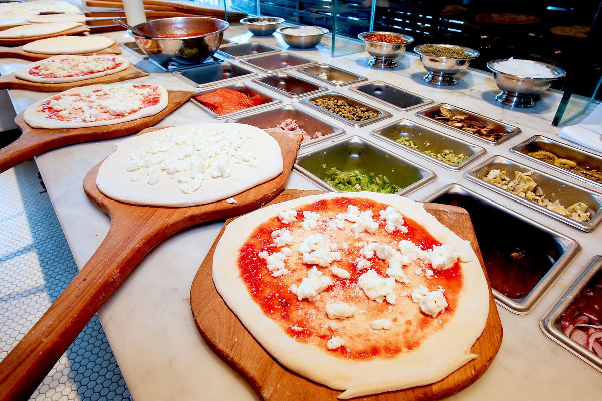 Pizzas lined up on a counter for topping