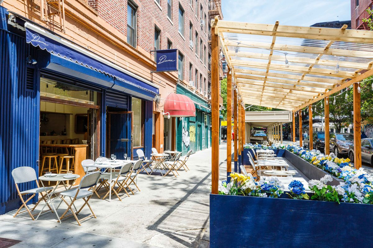 A blue restaurant facade with white tables and chairs on the sidewalk out front. A painted plywood patio sits curbside on the sidewalk with blue, white, and yellow flowers planted around the edges.