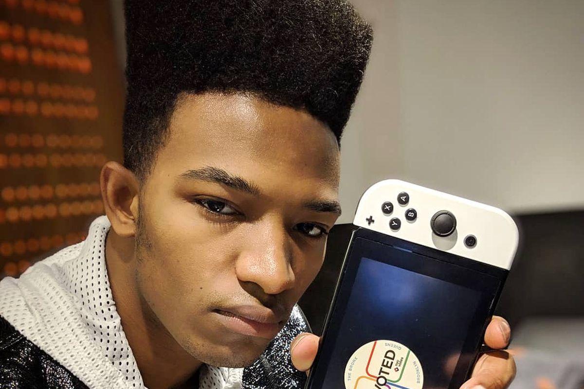 "Desmond ""Etika"" Amofah holds up a Nintendo Switch"