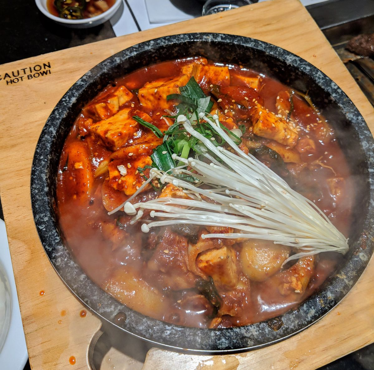 A claypot full of red broth and fish.