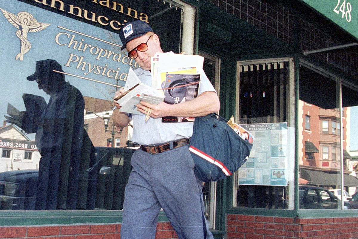 Letter carrier Don Dahlstrom examines his deliveries as he walks a route on Atwells Avenue in Providence, R.I., Friday, April 7, 2000. Letter carriers around New England are being forced to walk more of their routes because of repeated accidents in which parked mail trucks rolled away. (AP Photo/Jon Mahoney) ORG XMIT: BX104