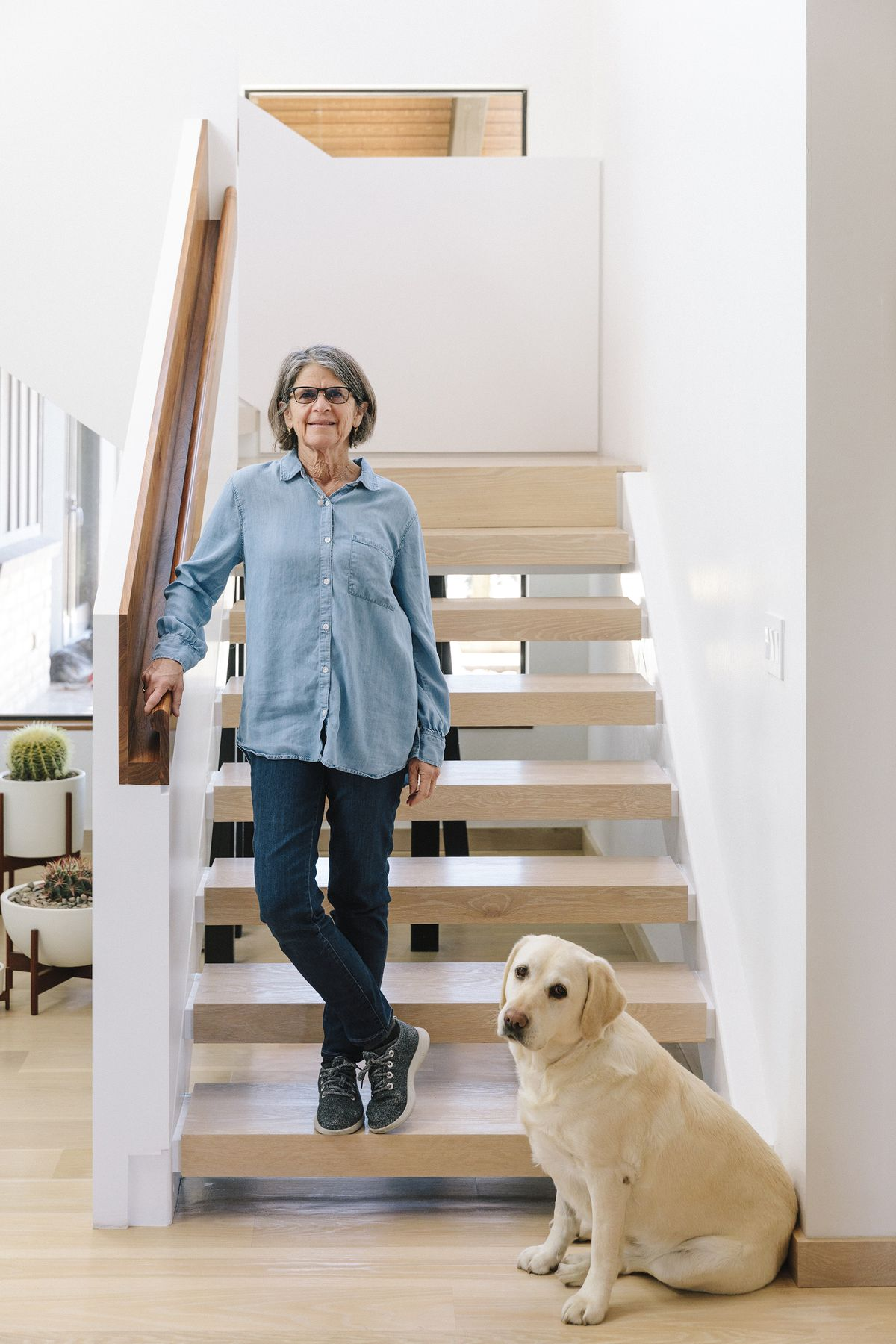 The homeowner, a woman, stands on a staircase looking at the camera. A dog stands on the staircase next to her. The stairs are wooden and the walls are painted white.