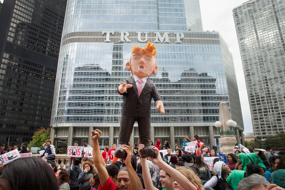 Demonstrators hold up a piñata of Republican presidential candidate Donald Trump during a protest outside Trump Tower.