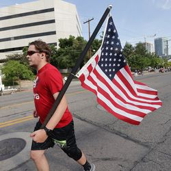Mitchell Williams carries an American flag while competing in the Deseret News Half Marathon in Salt Lake City on Friday, July 23, 2021.