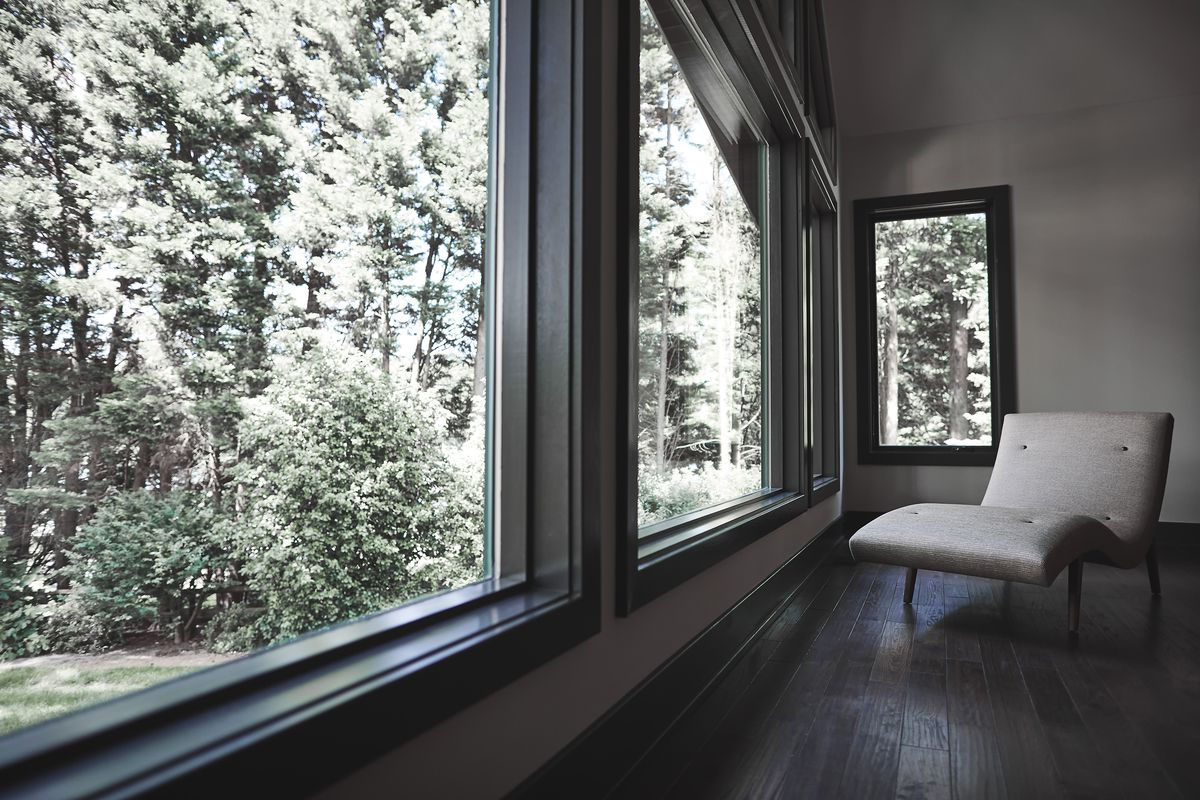 Floor to ceiling window with view of trees outside.