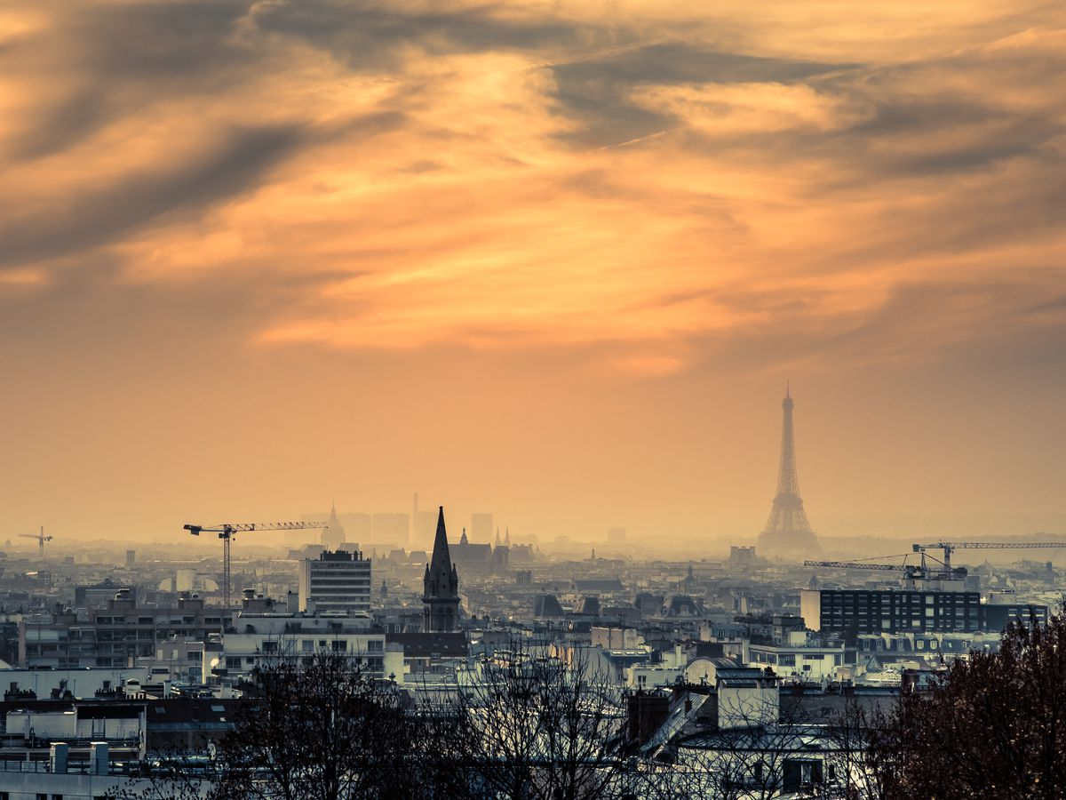 An aerial view of the city of Paris. There are many trees and buildings in the foreground. In the background is the Eiffel Tower and a sunset in the sky.