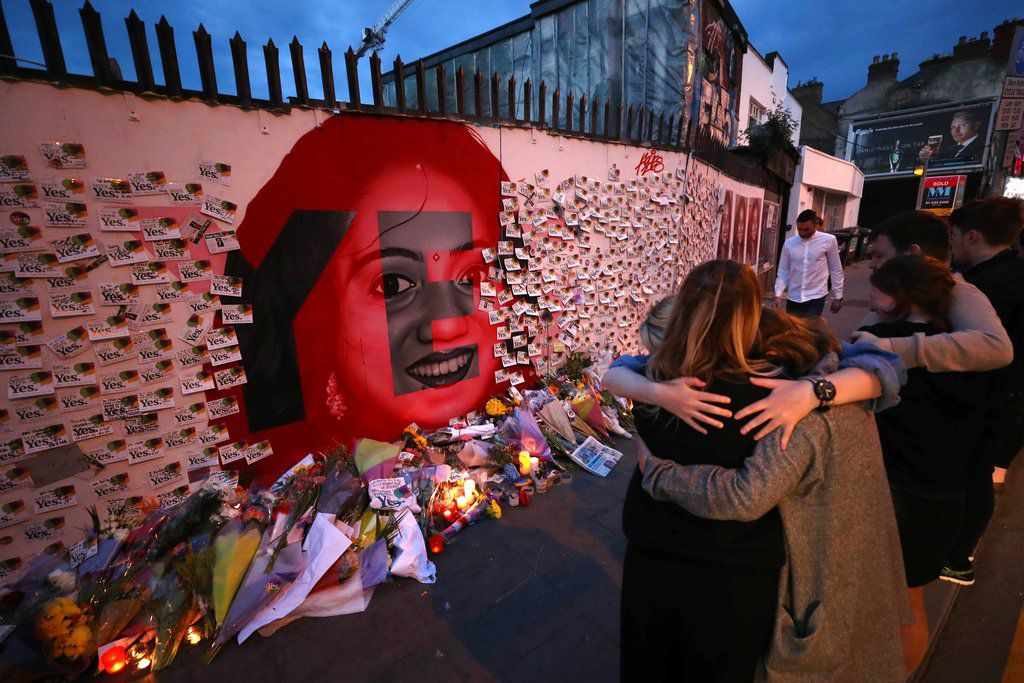 Candles and flowers are placed in front of a mural of Savita Halappanavar in Dublin, Ireland, Saturday, May 26, 2018. | Niall Carson/PA via AP