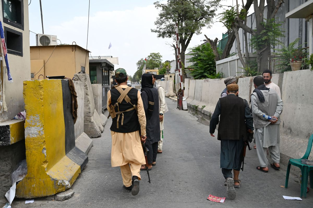 Four men facing away from the camera carry military rifles along an empty street, flanked by concrete barriers.
