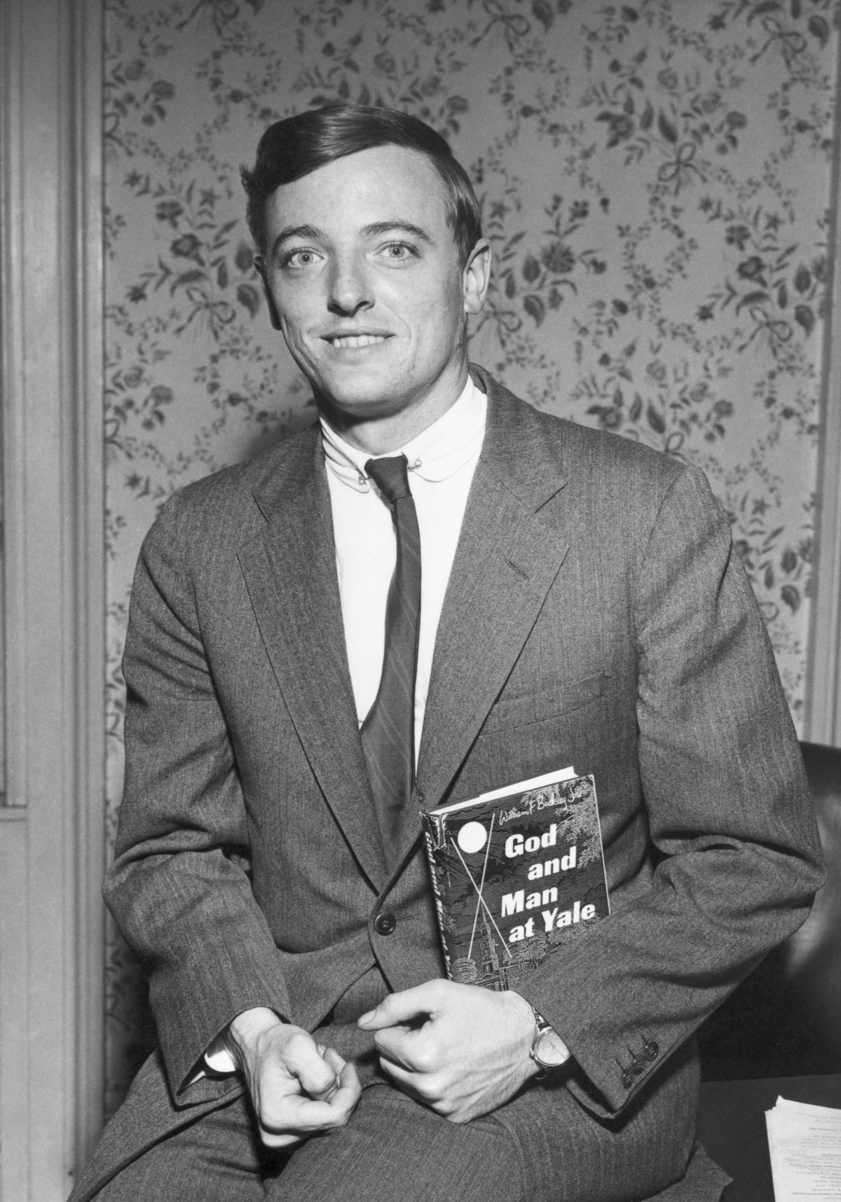 """A portrait of William F. Buckley Jr. with his first book, """"God and Man at Yale."""""""