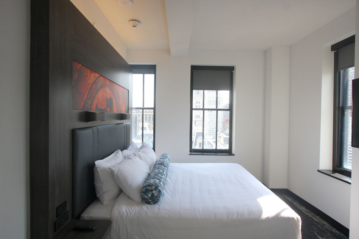 The interior of a room at Aloft Philadelphia Downtown. There is a bed with white bed linens, windows, and a colorful work of art on the wall.