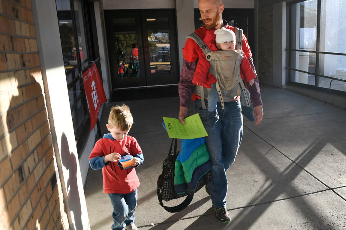 Skinner Middle School math teacher Peter English walks out of the Riverside Baptist Church with his son, Landon, left, and daughter Brooke strapped to his chest after voting on whether to go on strike ()