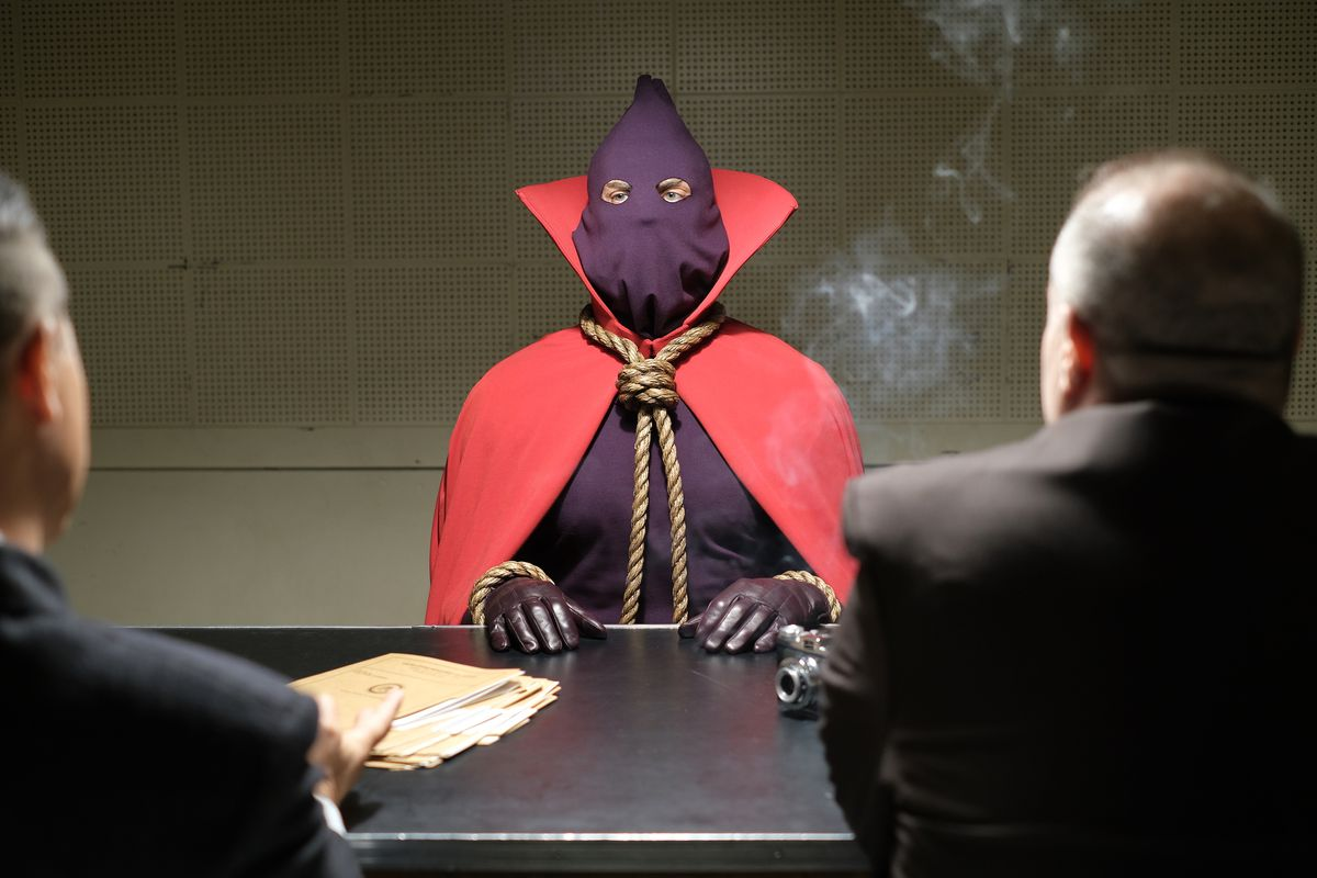 A person wearing a hood and a cape and a rope noose as a necktie sits at an interrogation table begin questioned by two conventionally suited men.
