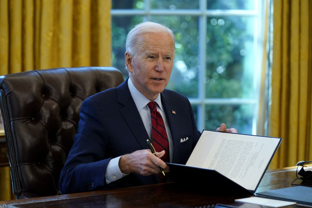 President Joe Biden signs a series of executive orders on health care, in the Oval Office of the White House, Thursday, Jan. 28, 2021, in Washington.