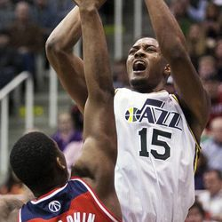 Utah's Derrick Favors yells as he shoots over Washington's Kevin Seraphin as the Jazz and the Wizards play Jan. 23 at EnergySolutions Arena. The Jazz won 92-88.