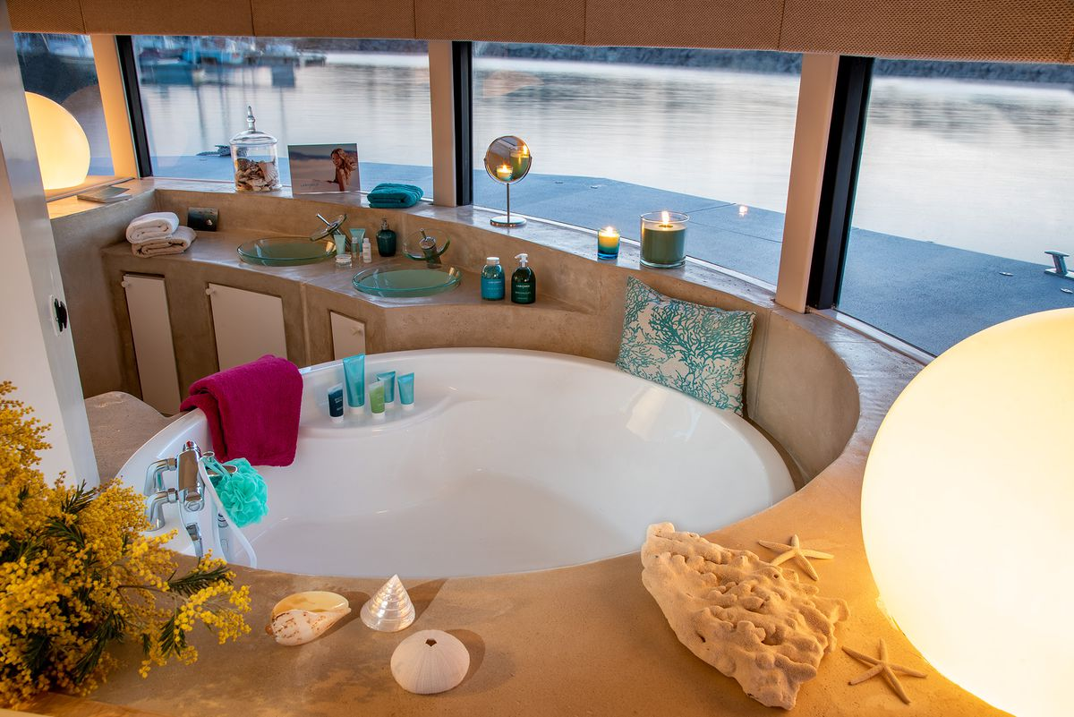 Круглая ванна, окруженная прямоугольными окнами, выходящими на океан.