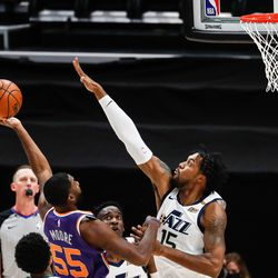 Utah Jazz center Derrick Favors (15) tries to block a shot from Phoenix Suns guard E'Twaun Moore (55) during an NBA preseason game at Vivint Smart Home Arena in Salt Lake City on Saturday, Dec. 12, 2020.