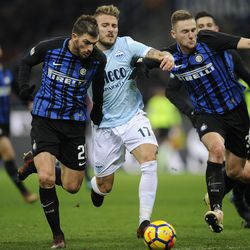 Ciro Immobile of SS Lazio compete for the ball with Milan Skriniar and Davide Santon of FC Internazionale during the serie A match between FC Internazionale and SS Lazio at Stadio Giuseppe Meazza on December 30, 2017 in Milan, Italy.