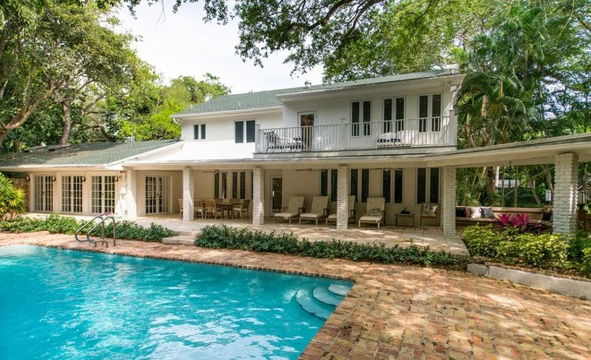 A two-story white colonial style home's backyard pool area in Coconut Grove.