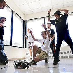 Instructor Morgan Reynolds, left, and students Carson Crook and Blake Ferris get excited about battling robots.