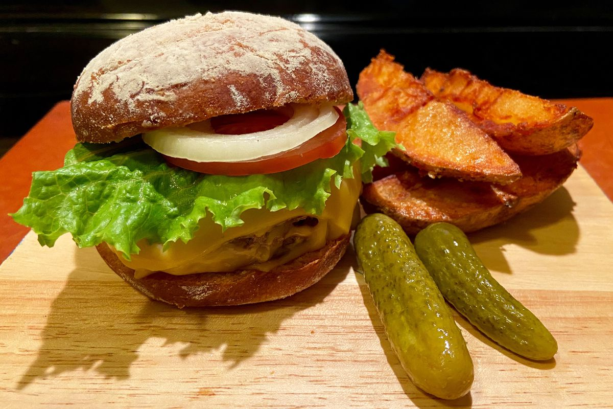 A double cheeseburger topped with lettuce, tomato, and onion on a wood carving board beside steak fries and two whole pickles