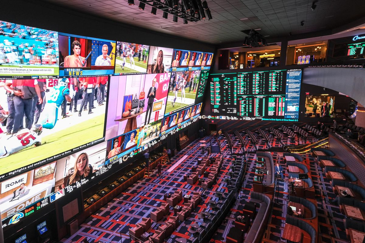 A view of a sportsbook with TV screens on the left, wagers on the right, and stadium-style seating below.