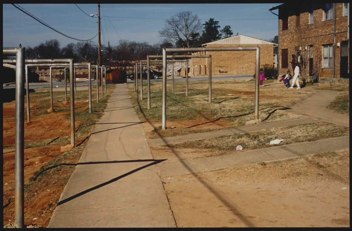 A series of dirt yard with large metal poles in the yards.
