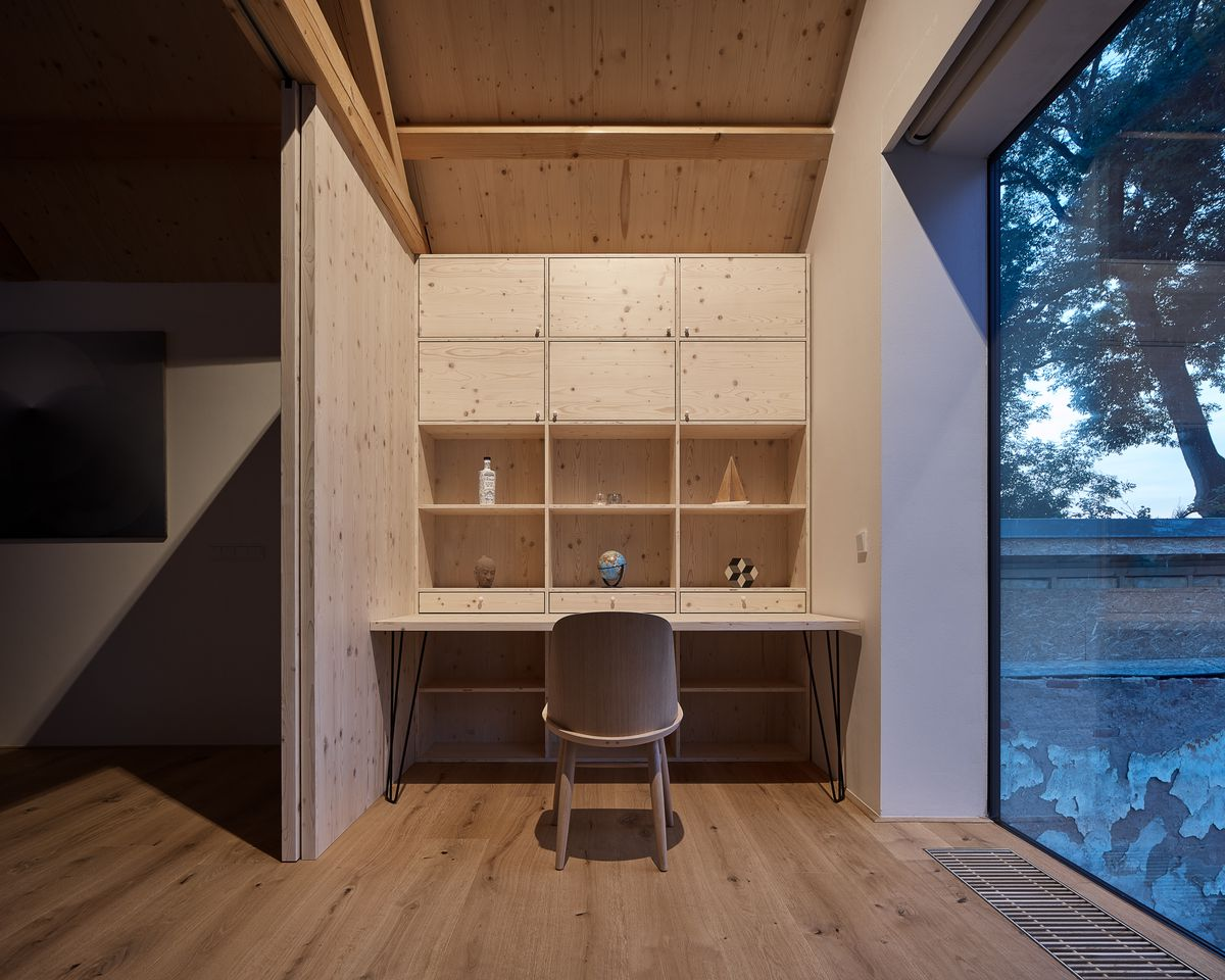 Office nook with built-in bookshelves in pale wood, and large glass window.
