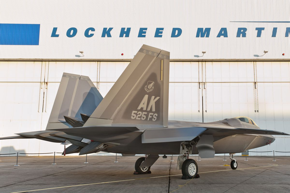 An F-22 in front of the Lockheed Martin hangar.