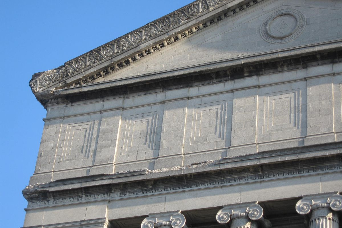 A close up photo of the top of a building with carved stone detailing. There is a triangular top with square column carving.