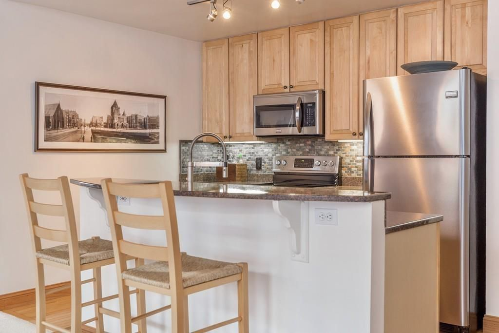 A close-up of a small kitchen with a large, tall counter with stools in front of it.