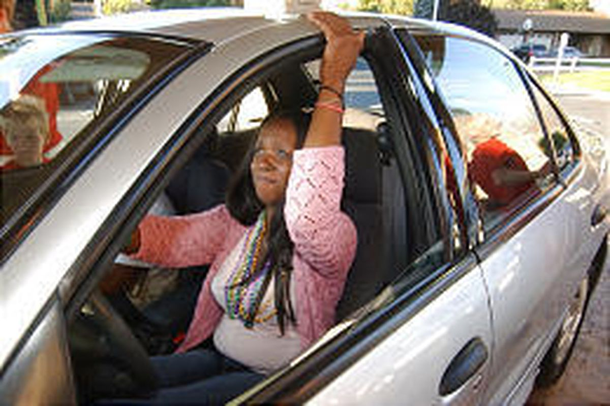An overwhelmed Kathy Phipps sits in a 2002 Pontiac Sunfire donated to the New Orleans evacuee by Low Book Sales of Lindon.