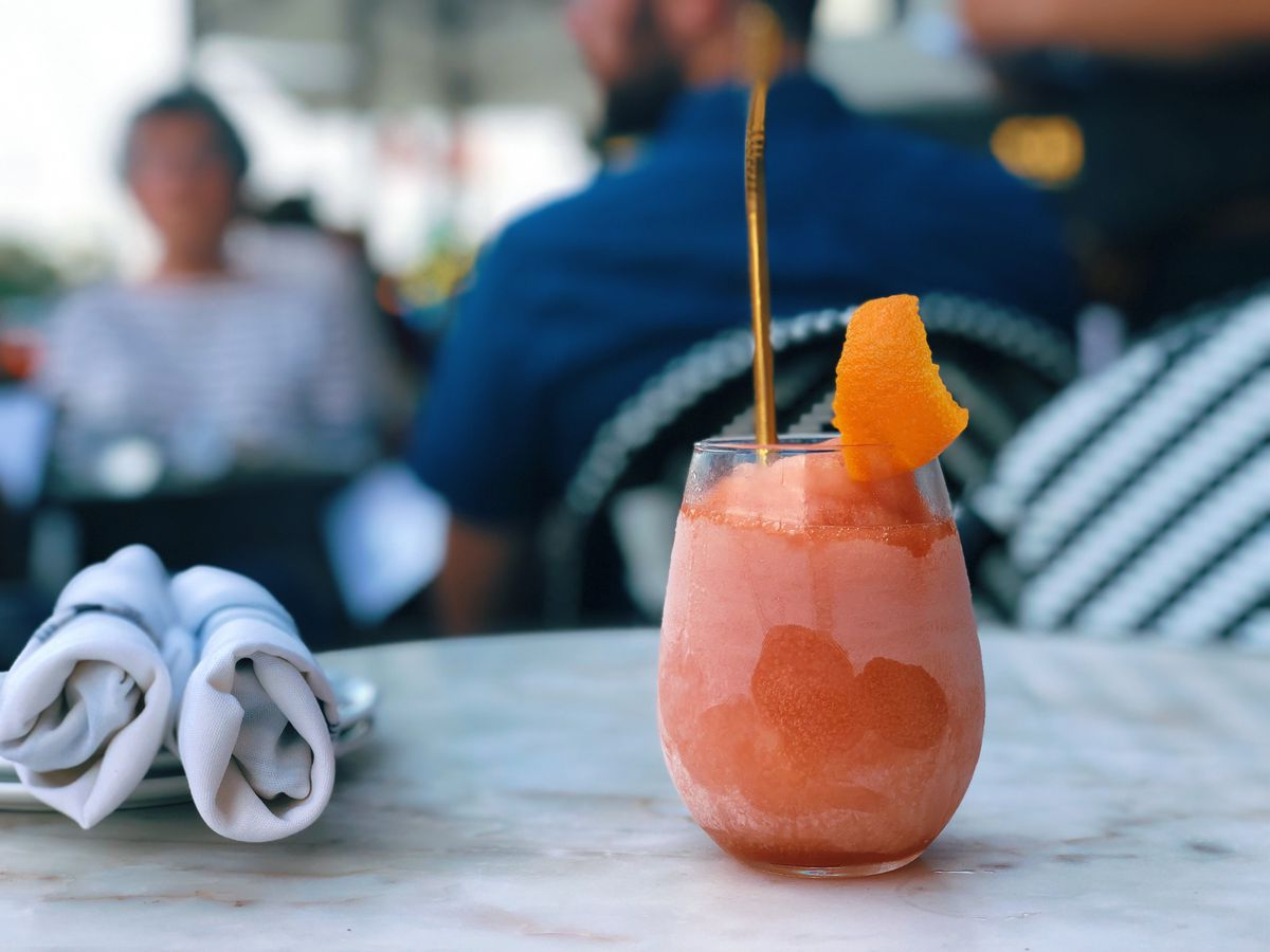 A pink frozen Negroni sits on a marble table on a restaurant's patio. It's in a stemless wine glass, garnished with orange rind. A few diners are visible, blurred, in the background.