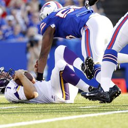 Aug 16, 2013; Orchard Park, NY, USA; Minnesota Vikings quarterback Christian Ponder (7) is sacked by Buffalo Bills defensive end Jerry Hughes (55) during the first quarter at Ralph Wilson Stadium.