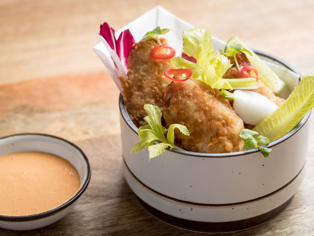 The wings at Jeju Noodle Bar are in a white bowl, with a small container for sauce nearby.