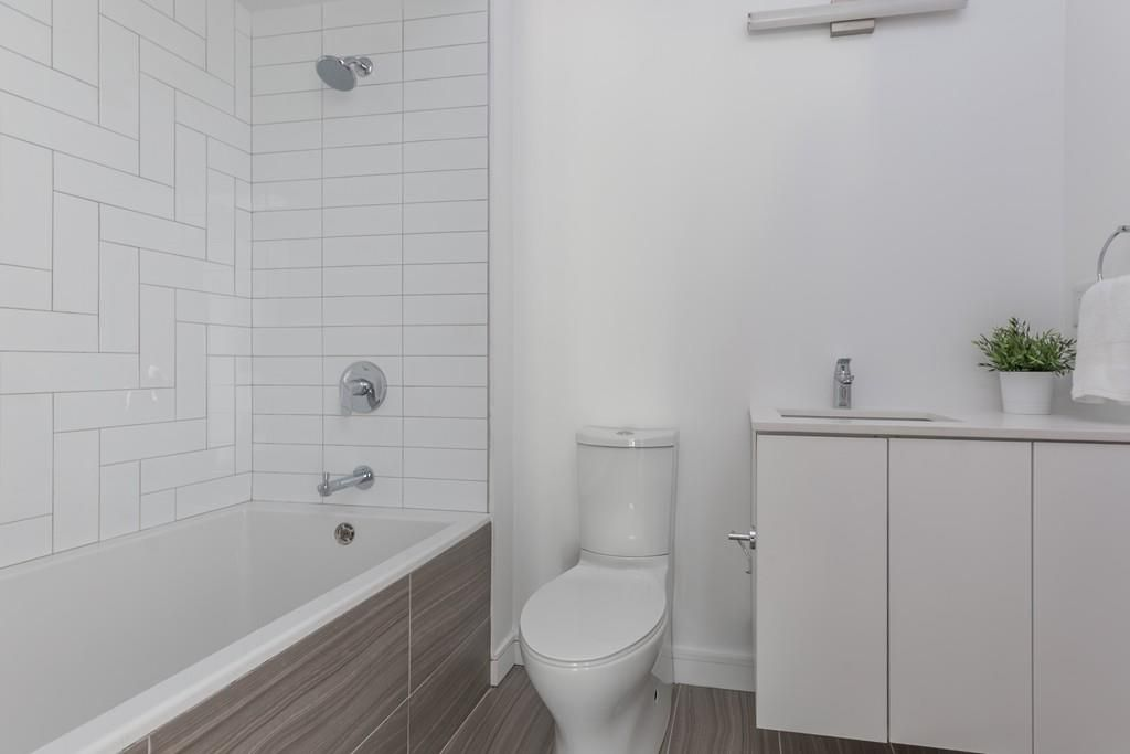 A bathroom with a toilet next to a shower with half a glass door on it.