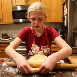 Camree Kirby rolls out cookie dough during a family night at the family's home in Lehi on Thursday, Dec. 17, 2020.