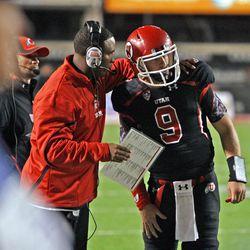 Assistant coach Brian Johnson talks with Utah quarterback Jon Hayes in a game last season.