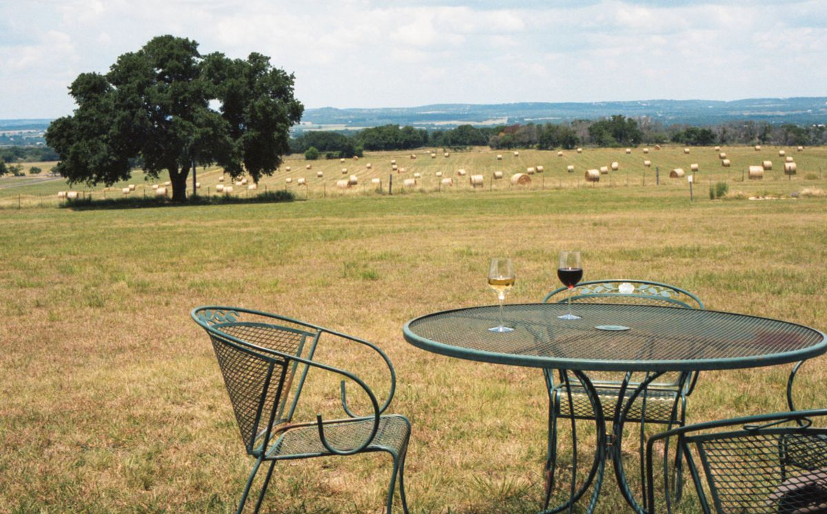 In the foreground, a green wrought-iron circular table and chairs are set with two glasses of wine amid a wide expanse of land with a tree in the background and haybales in the fields beyond it.