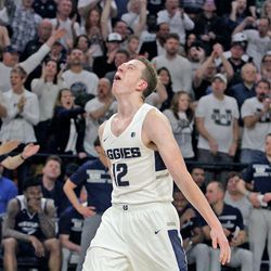 A jubilant Justin Bean (12) heads up the court at the Spectrum during the final moments of Utah State's 81-76 upset of the No. 12 Nevada on March 2, 2019, in Logan.