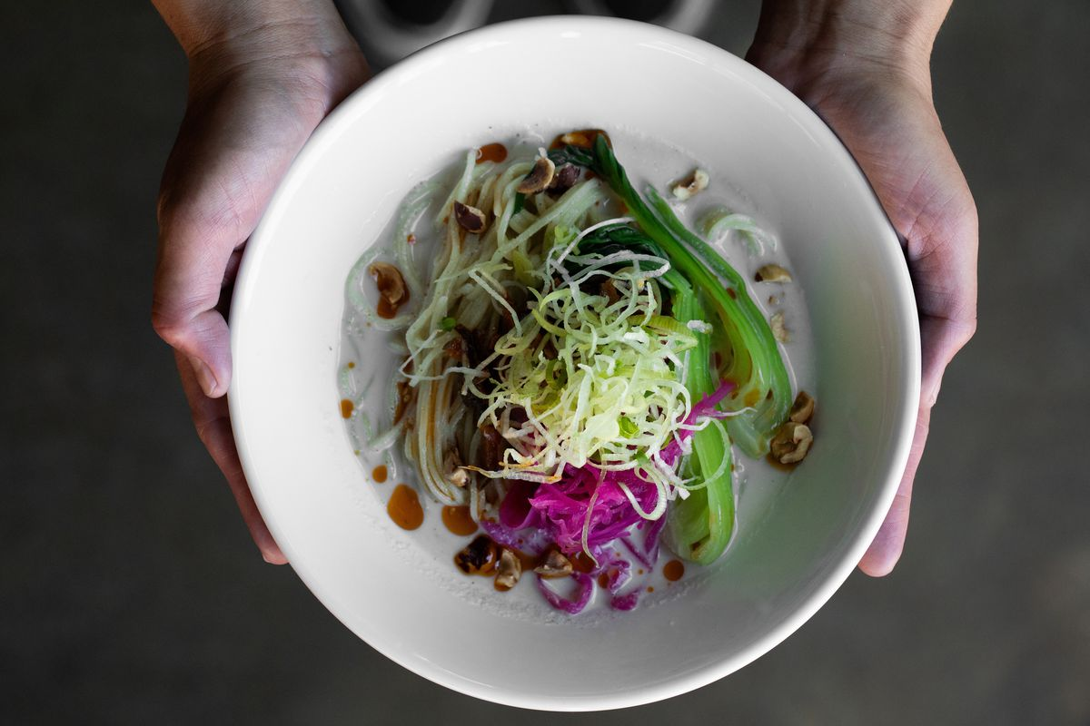 Two hands hold a bowl of noodles with vegetables at Kinboshi ramen