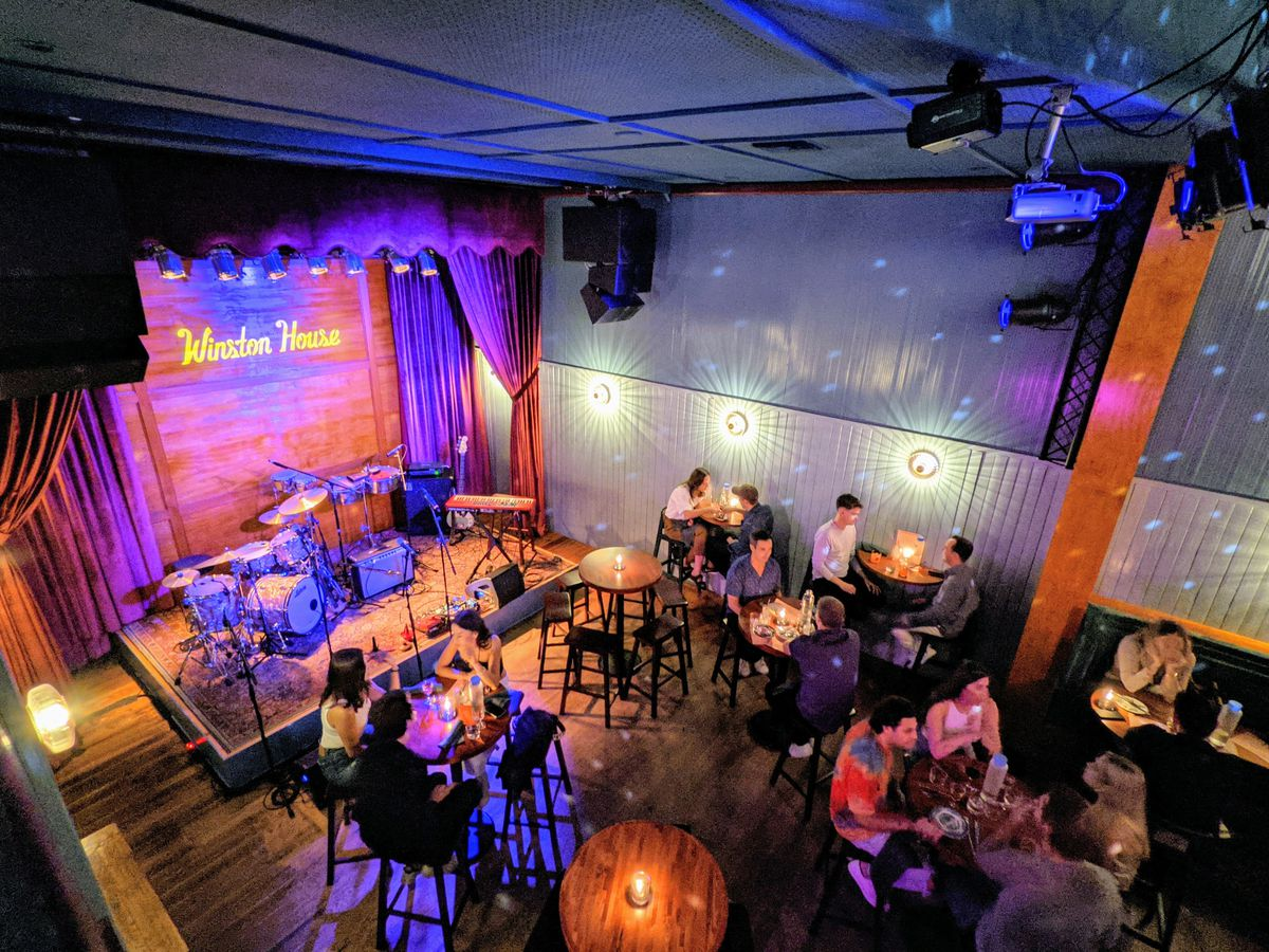 A music venue with purple lights, a stage, and small tables surrounding the stage.