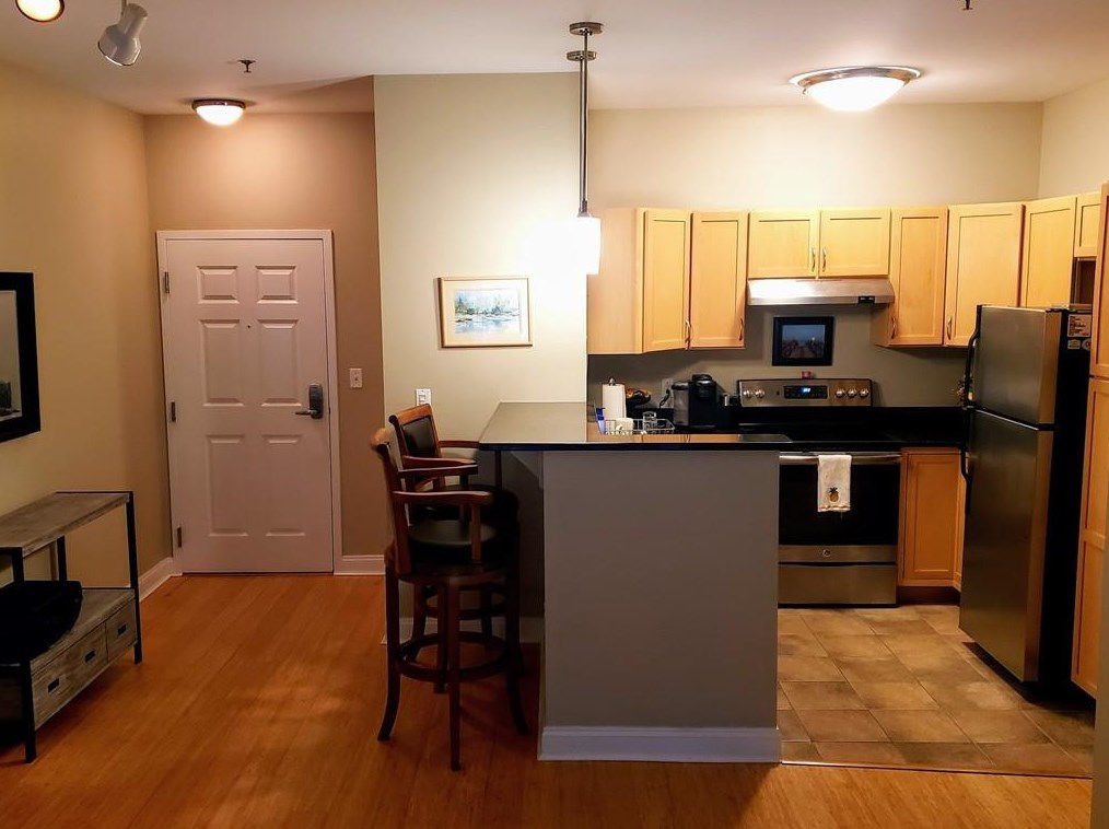 An open kitchen with a U-shaped counter and stoops in front of one part of the counter.
