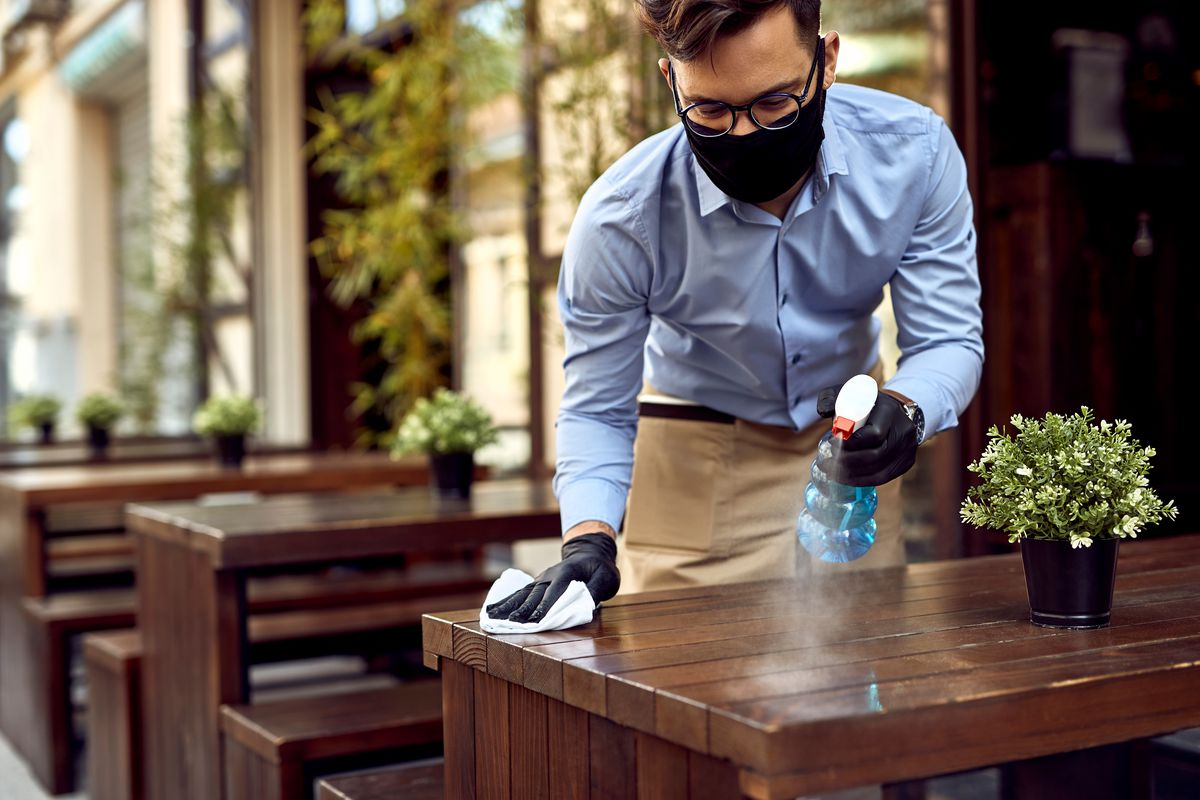 A waiter in glasses and a blue button-down shirt wears a black protective mask while disinfecting tables on an outdoor patio