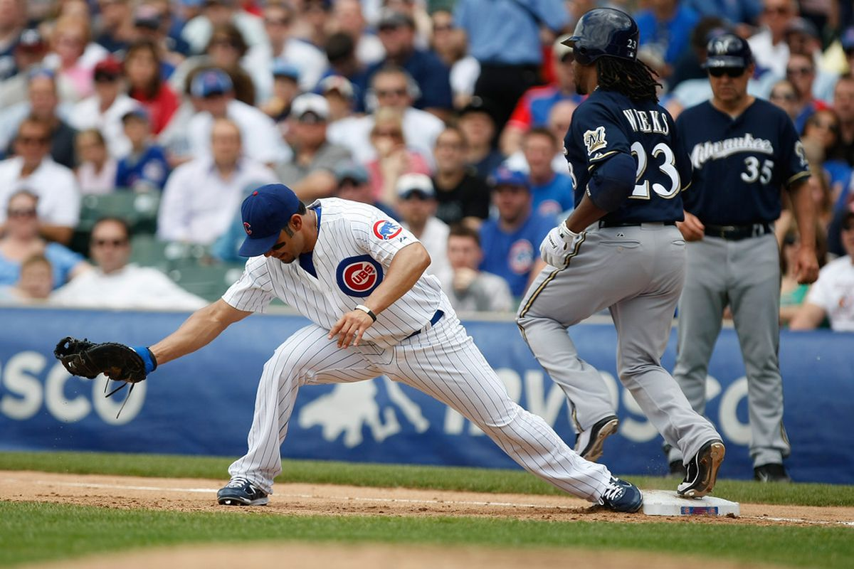 Carlos Pena of the Chicago Cubs catches the baseball for an out at first base as Rickie Weeks of the Milwaukee Brewers runs at Wrigley Field on June 16, 2011 in Chicago, Illinois. (Photo by Scott Boehm/Getty Images)