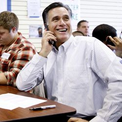 Republican presidential candidate, former Massachusetts Gov. Mitt Romney sits with volunteers and calls likely voters ahead of Tuesday's primary election, Monday, Jan. 9, 2012, during a visit to his campaign headquarters in Manchester, N.H.