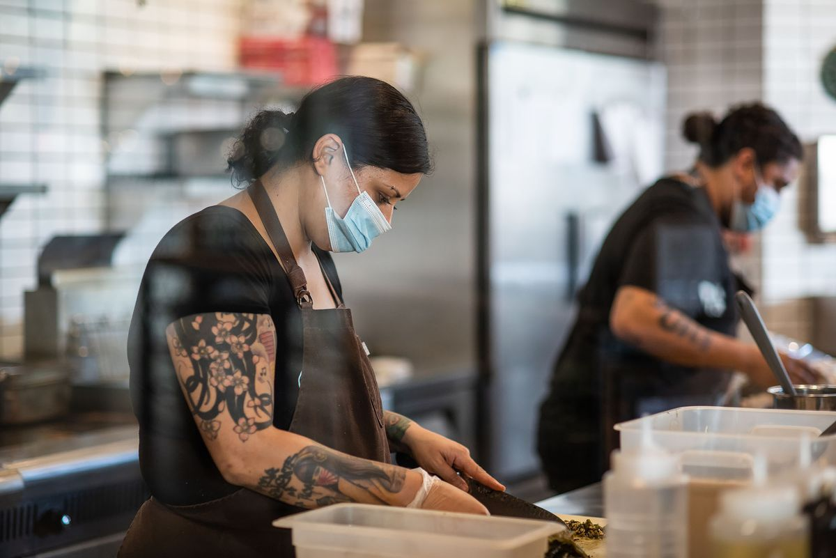 Worker prepares takeout food at Taco Maria