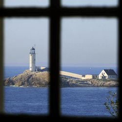 In this photo taken Friday, Sept. 14, 2012, the lighthouse on White Island can be seen through the church window at the historic Star Island Family Retreat and Conference Center at the Isle of Shoals in Rye, N.H. The hotel 10 miles off the coast of New Hampshire wants to establish itself as an environmental leader. The island is essentially a self-contained system, and it is an ideal spot to showcase energy innovations and could be become a model for other communities.