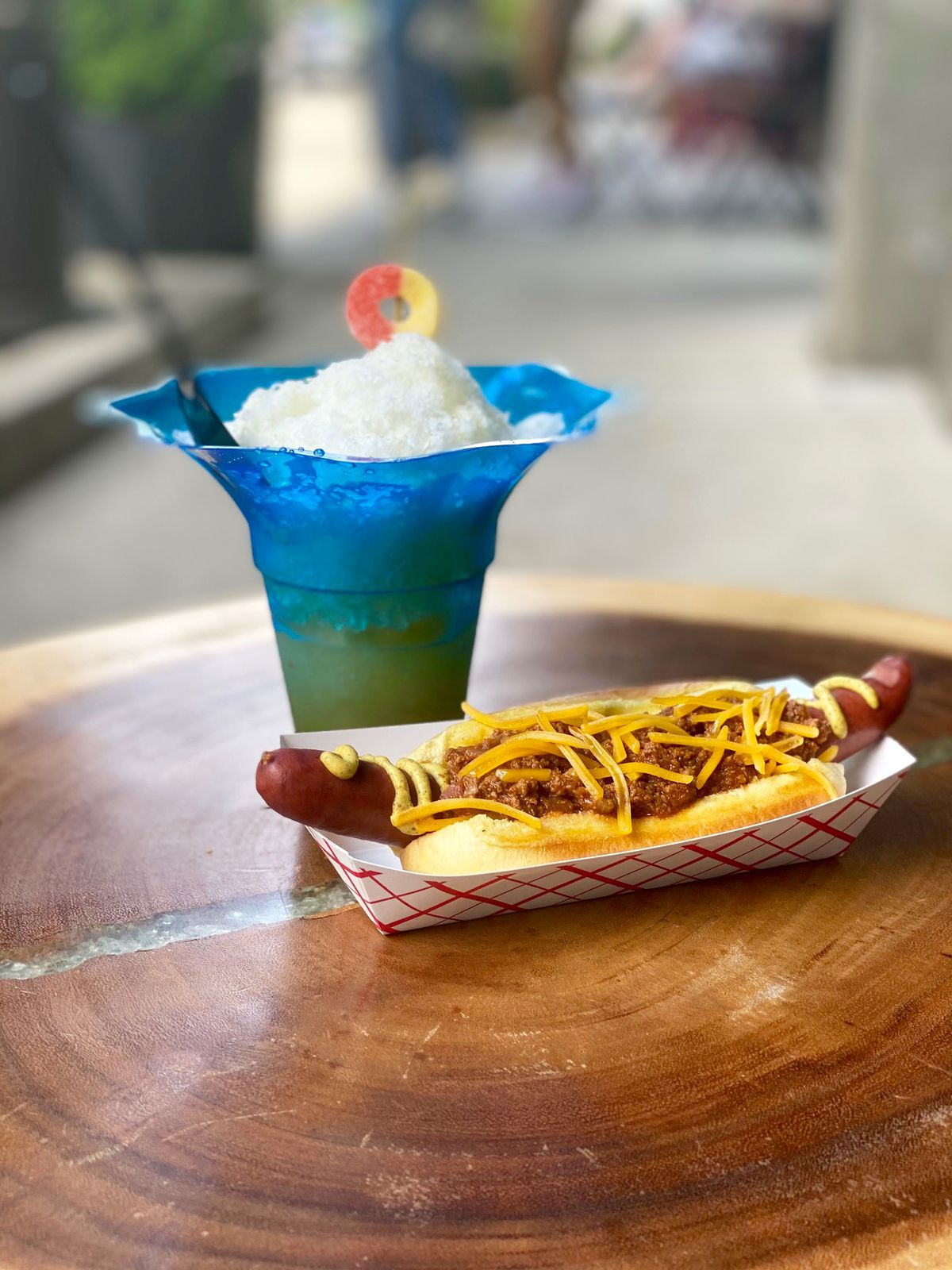 The Cream Peach cocktail in a blue glass ice cream dish with a peach ring garnish made with bourbon, Aperol, lemon, mint, allspice dram, sugar, condensed milk. The hot dog pictured with that cocktail is the chili dog - house made chili, sharp cheddar, spicy mustard.